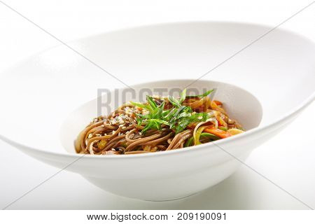 Asian food restaurant. Buckwheat noodles with chicken vegetables sprinkled with fresh herbs and sesame seeds in white plate.