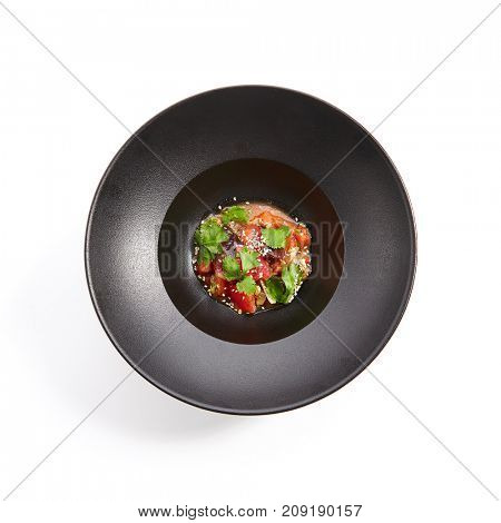 Pan-Asian menu in  restaurant. Eggplant in Asian style with the addition of tomato sesame and fresh herbs in an iron bowl. Top VIew