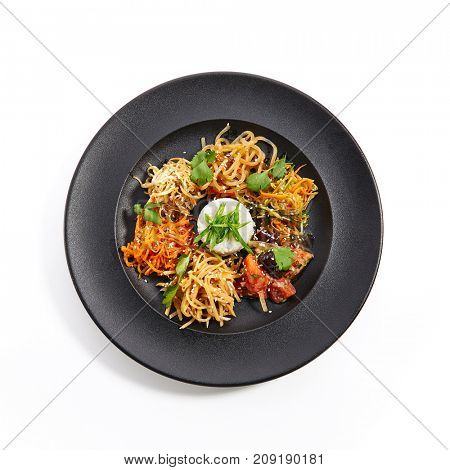 Set of vegetable snacks in Asian style with sesame and fresh herbs on an black plate. Pan-Asian cuisine in  restaurant. Top View