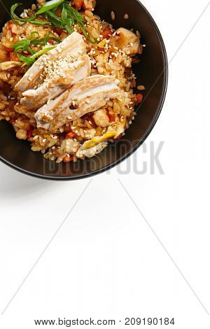 Fried rice with chicken vegetables fresh herbs and seasonings in dark bowl. Pan-Asian cuisine in restaurant. Top view