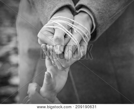 child's hand reaches out to the rope-tied hands of the parent. Black and white image. Woman's hands tied with rope. Violence in family concept