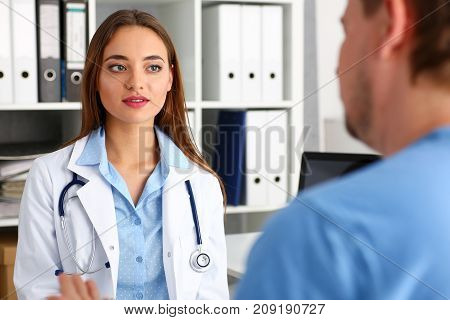 Beautiful concerned female doctor talk with male visitor during ward round check in office. Medic exam aid and remedy prescribe for sick business problem and healthy lifestyle advice for anamnesis