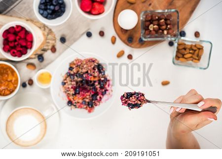 Top view showing hands eating porridge with honey nuts, blueberries on white table