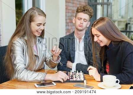 Group of teenagers having fun at the cafe and playing a chess game together on a blurred background. Difficult intelligence games for companies.