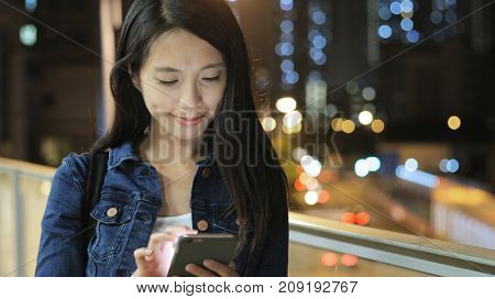 Woman using mobile phone in city at night