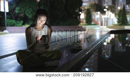 Woman using smart phone at night