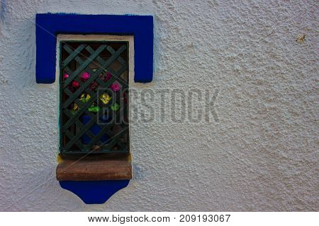 Window. Window with a flower in a pot. Traditional Spanish architecture. Costa del Sol, Andalusia, Spain. Picture taken - 15 october 2017.