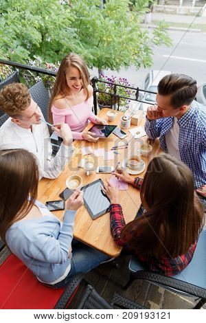 Group of busy, active students doing homework together at the cafe, with tablet computers and smartphones and chatting on a blurred background.