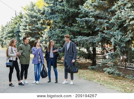 A group of best friends together and walk in the park. Friends all have a good time and smile. Concept of leisure.