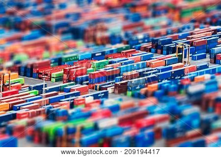 Texture made with an aerial view over shipping cargo containers stacked on a commercial port. Tilt-shift effect applied suitable to be used as background