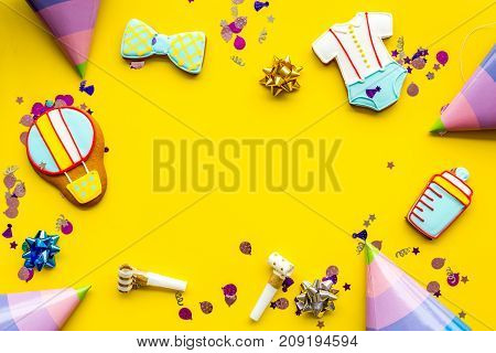 Cook gingerbread cookies with ticker tape for baby shower on yellow colorful desk background top view mockup poster