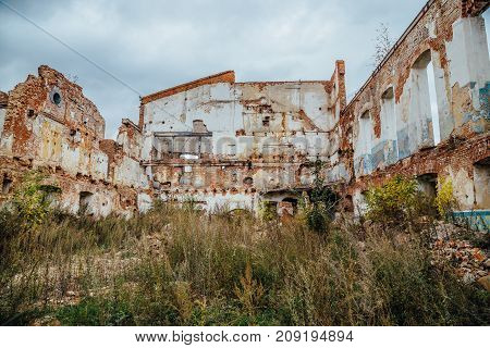Ruined and overgrown by plants red brick industrial building. Abandoned and destroyed sugar factory in Novopokrovka, Tambov region