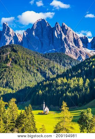 Dolomites, Tirol.  Sunny day. The symbol of the valley Val di Funes - church of Santa Maddalena. Rocky peaks and forested mountains surrounded by green Alpine meadows
