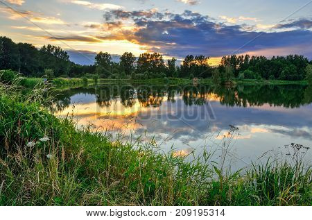 Beautiful summer landscape. Pond in the countryside in fabulous evening colors.