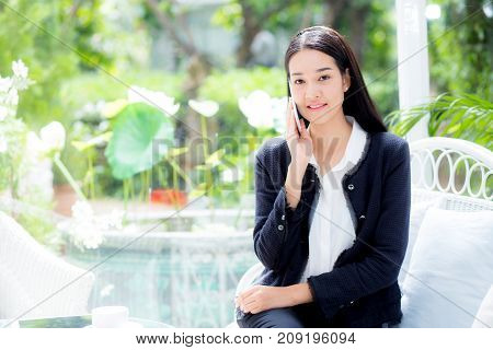 Portrait Of Woman Sitting At Sofa While Talking A Call At Home - Business People.