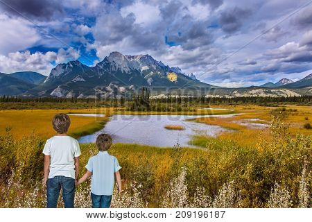 Magnificent landscape in the Rocky Mountains. Two boys admire the mountains and lakes. The concept of ecological and active tourism