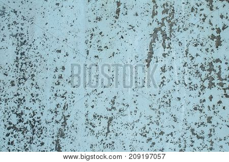 Old weathered grunge metal blue painted tin metal surface with cracked paint closeup as background