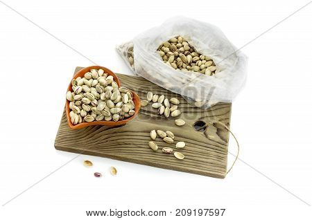 Pistachios in a bowl and in a sack on a white background closeup