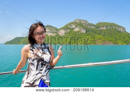 Cute young woman with eyeglasses thumb up the beautiful natural of the sea island and sky in summer on the boat while cruising at Mu Ko Ang Thong National Park Surat Thani Thailand