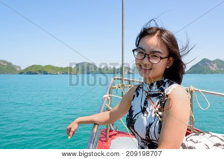 Cute young woman with eyeglasses smiling happily on the prow boat while cruising the beautiful natural of the blue sea and sky in summer at Mu Ko Ang Thong National Park Surat Thani Thailand