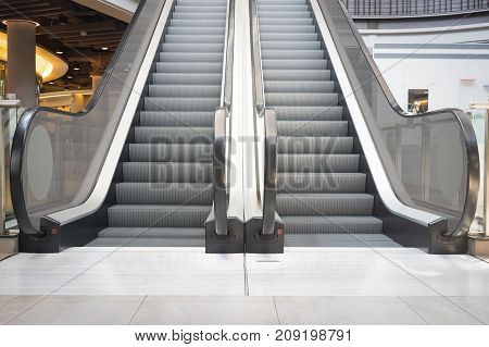 Escalator step and white tile floor inside building.