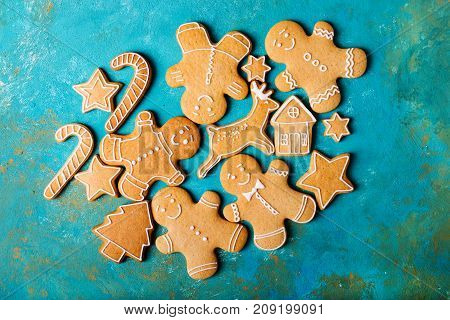 Ginger men with colored glaze on a turquoise background .. Gingerbread. Christmas cookies. Ginger man in a colored sweater.