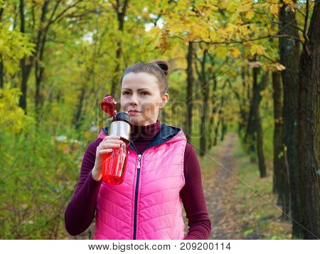 Beautiful fitness sport girl in autumn park in sportswear drinks water or isotonic drink from a sports bottle