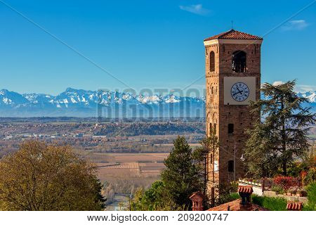 Old belfry overlooking autumnal landscape as mountain ridge on background under blue sky in Piedmont, Northern Italy.
