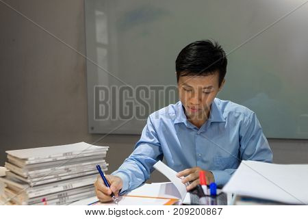 The boss taking note in sales report in the meeting room