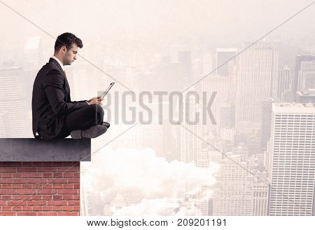 An elegant businessman in modern suit sitting on the top of a brick building, looking over the cityscape with clouds concept