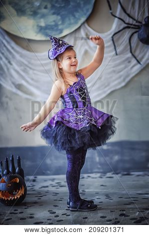 funny child Girl in witch costume a magic wand for Halloween on the background of immense spiders. pumpkin Jack