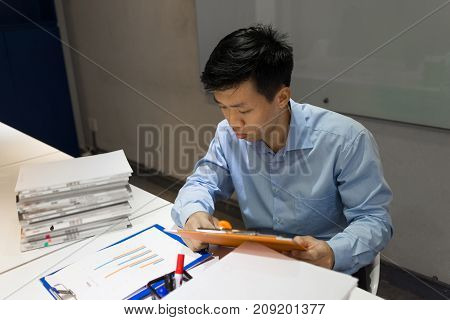 Office worker reading sales report in the office