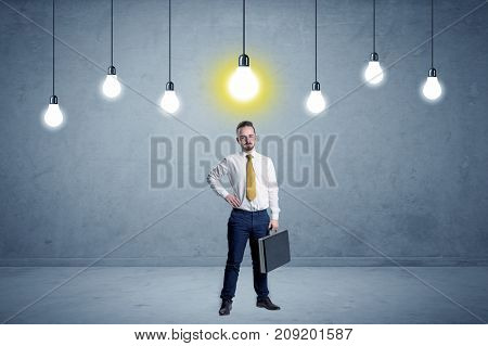 Handsome businessman in an empty space with bulbs above and uninspired face