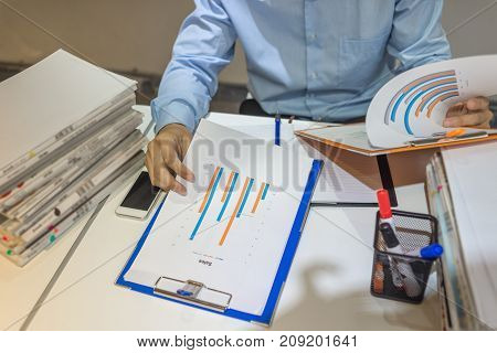 Business manager comparing two sales reports of company
