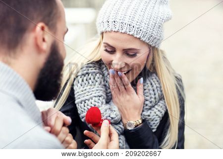Adult man giving engagement ring to beautiful woman
