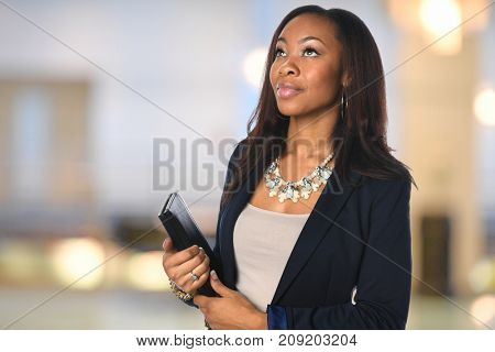 Portrait of African American businesswoman looking up inside office building