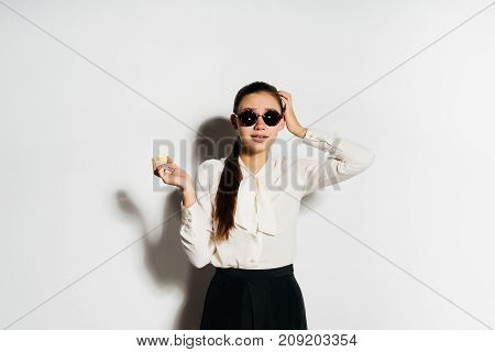 a cool girl in sunglasses and a white blouse holds a gold coin in her hands and looks directly into the camera. Bitcoins, crypto currency, electronic money.