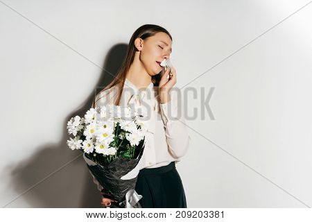 the girl is allergic to flowers. The lady covers her nose, sneezes. Beautiful bouquet of flowers. Allergy, disease.