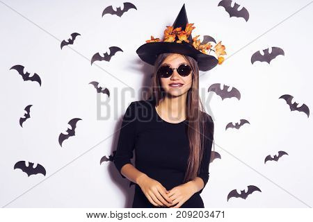 cool witch with glasses. Witch in a black dress and hat with fallen leaves. Girl on Halloween party. Halloween outfit, holiday.