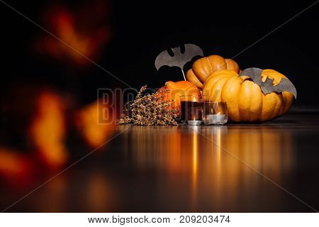 large Halloween pumpkins for a party. burning candles, dry branches on a black background. Halloween party, pumpkins