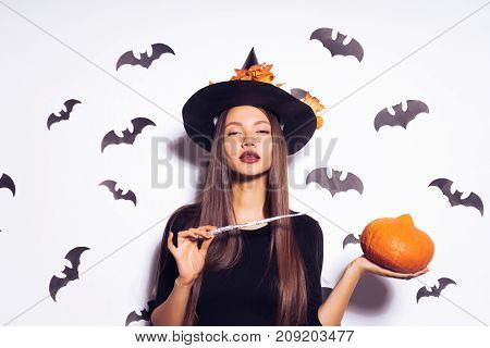 A steep witch conjures a pumpkin with his magic wand and looks into the camera. Witch in a black dress and hat with fallen leaves. Girl on Halloween party. Halloween outfit, holiday.