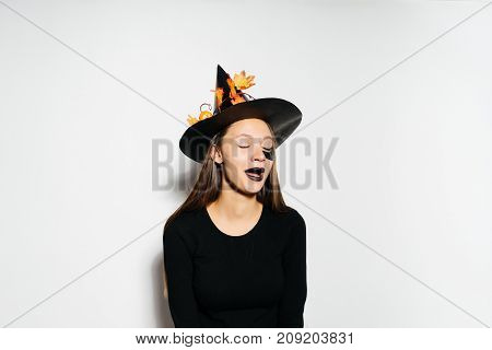 a funny beautiful witch with a big hat with autumn leaves looking away. Halloween style, Halloween party