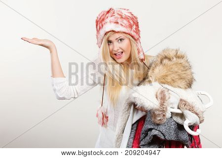 Woman In Winter Hat Holding Clothes Pile