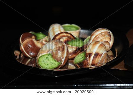 Escargots de Bourgogne on a metal plate in the oven
