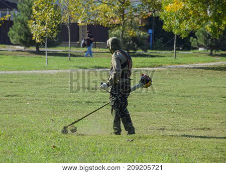 Krasnodar Russia - October 12 2016: A worker mowing grass with a gasoline brush. Trimmer. Mowing green grass using a fishing line trimmer. Application trimmers.