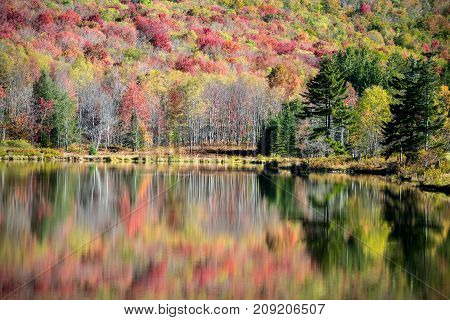 Colorful autumn trees and foliage reflected on the calm surface of a mountain lake.