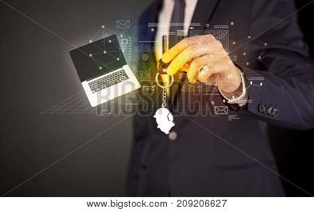 Businessman in suit holding keys with statistics, graphs and icons around