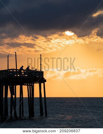 Fisherman try their luck shortly after sunrise at the Avon fishing pier on Hatteras Island North Carolina.