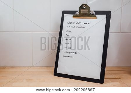 Chocolate cake recipe clip board on the table at kitchen. cake ingredients (chocolate eggs flour milk butter sugar cinnamon baking powder salt). Background layout with free recipe text space.