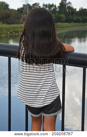 little girl with black hair standing at railing